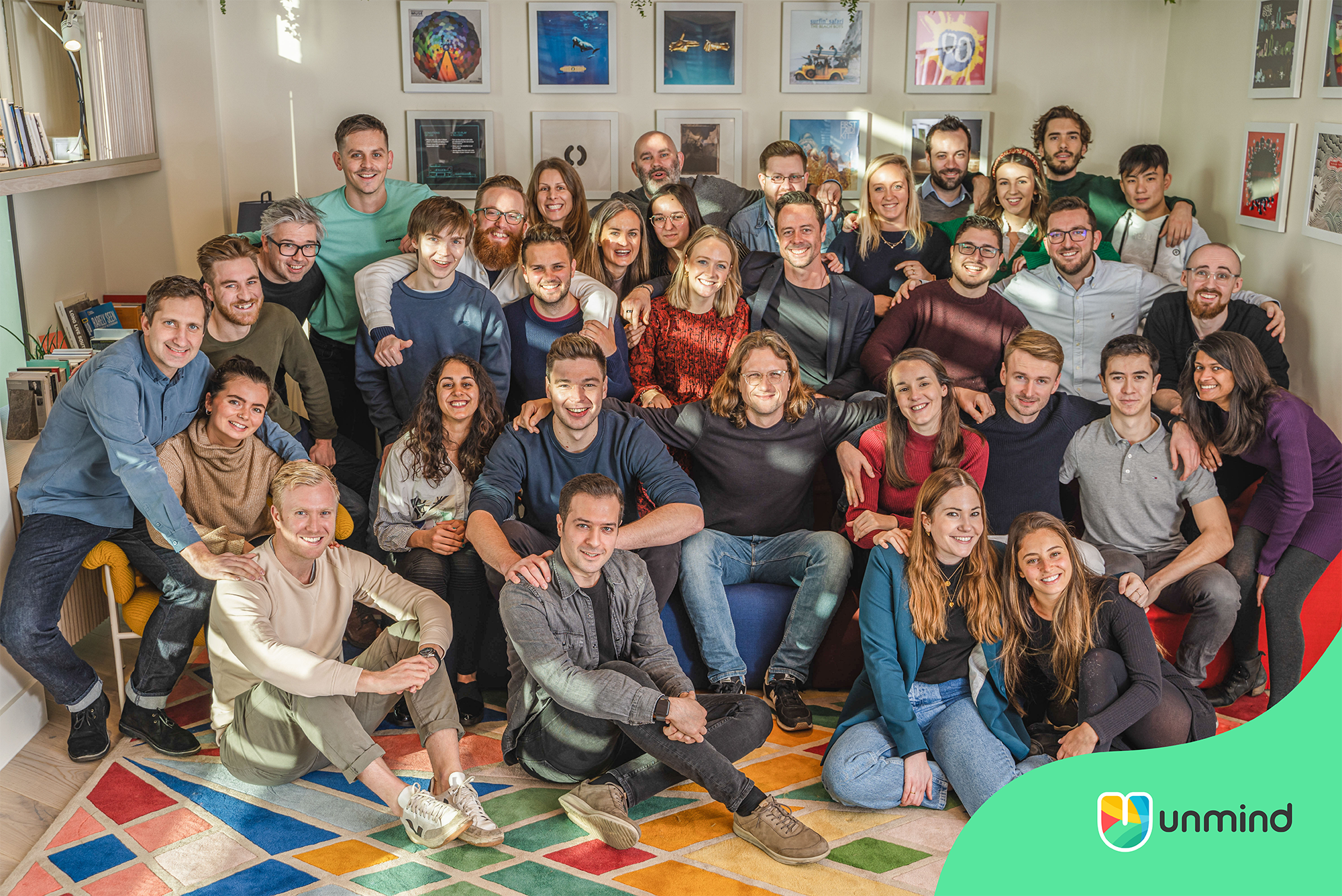 The Unmind team huddle to celebrate their successful Series A funding round in their UK office.